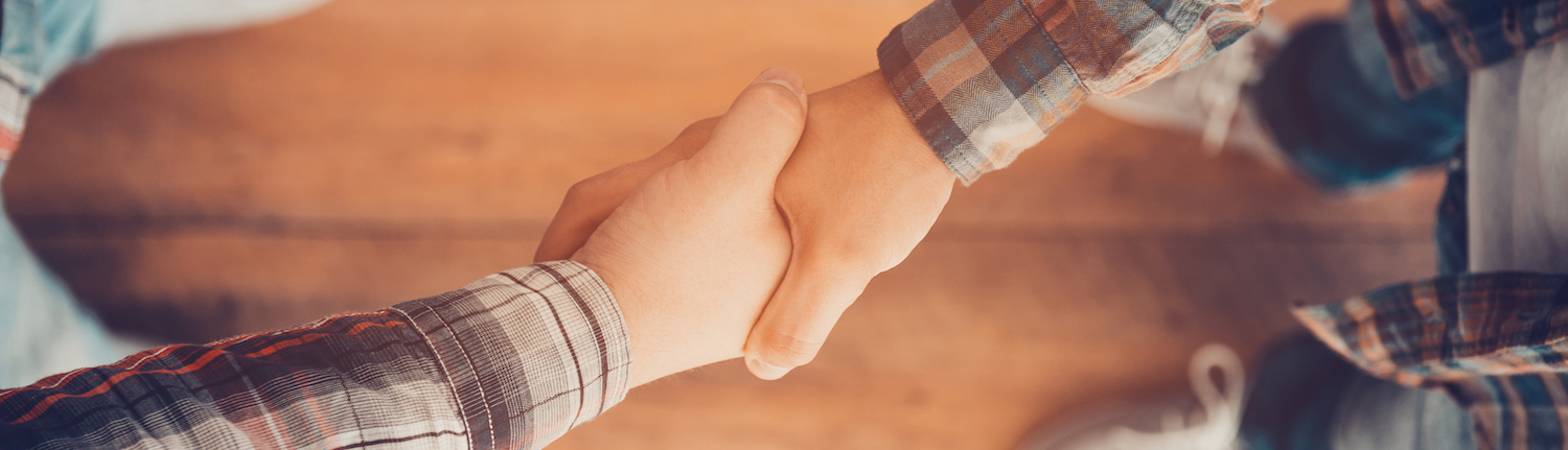 Men in flannel shirts shaking hands